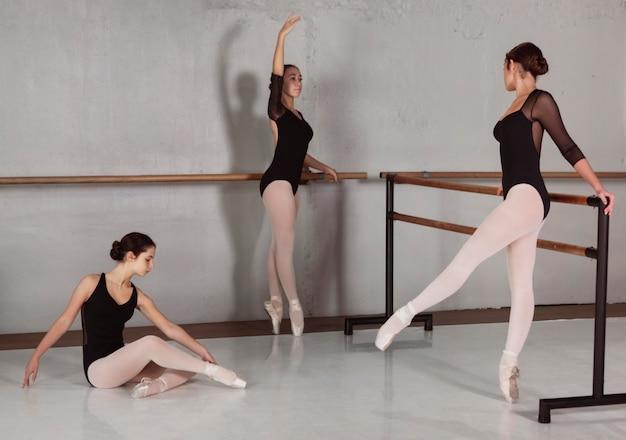Vue latérale de la formation de ballerines professionnelles avec des justaucorps et des pointes