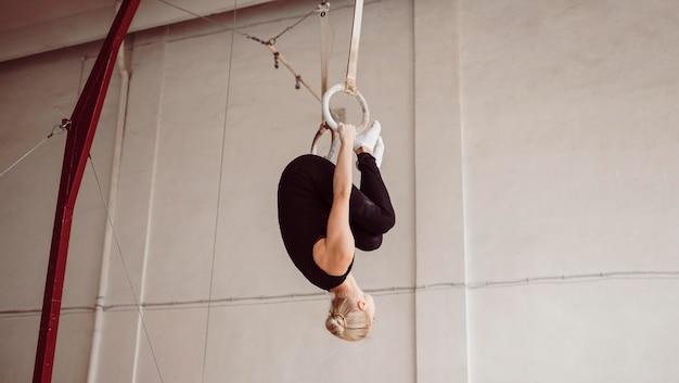 Vue latérale de la formation de femme athlétique sur les anneaux de gymnastique