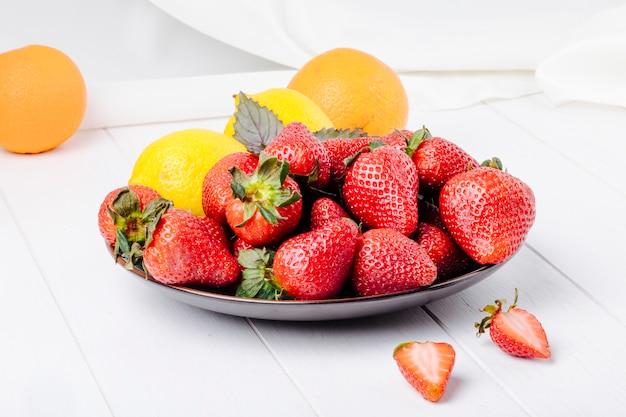 Vue latérale fraise au citron basilic et orange sur fond blanc