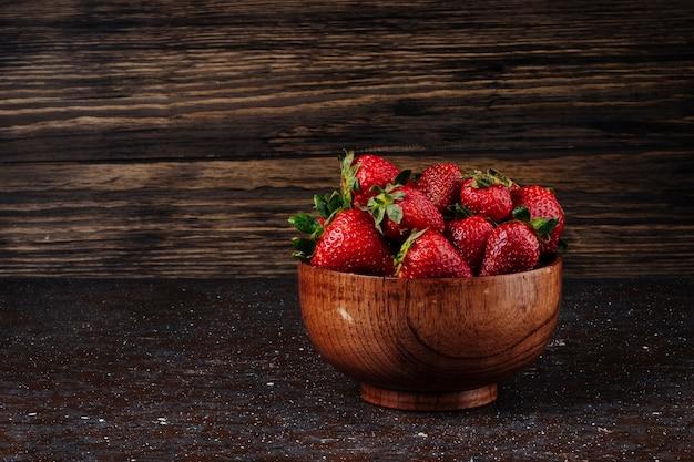 Vue latérale fraise dans un bol sur fond de bois
