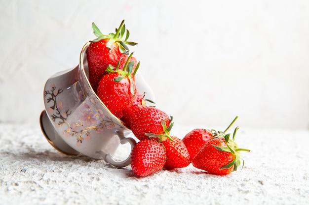 Vue latérale des fraises dans une tasse de café sur fond texturé blanc. espace de copie horizontal pour le texte