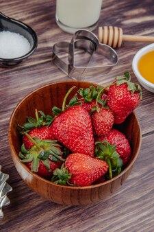 Vue latérale des fraises mûres fraîches dans un bol en bois avec emporte-pièces et miel sur rustique
