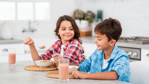 Vue latérale des frères et sœurs prenant son petit déjeuner