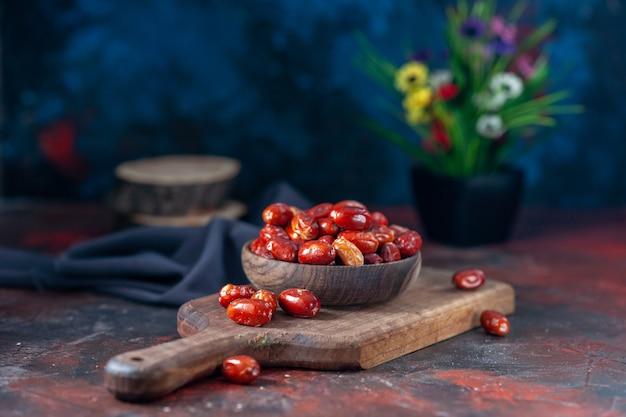 Vue latérale de fruits frais crus à l'intérieur et à l'extérieur d'un petit bol sur planche de bois et pot de fleurs sur fond de couleurs mélangées