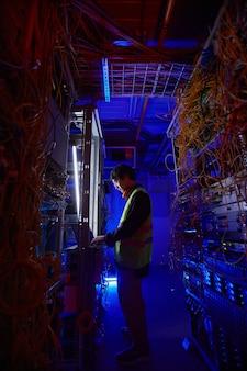 Vue latérale futuriste chez un jeune technicien réseau utilisant un ordinateur portable dans la salle des serveurs lors de la configuration de la connexion internet