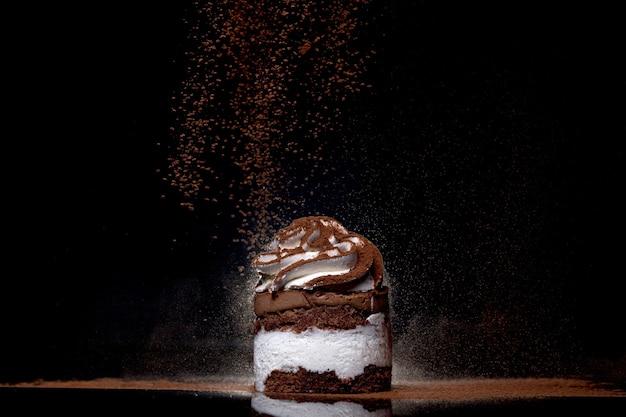 Vue latérale d'un gâteau au chocolat cuit au four parsemé de cacao sur le comptoir avec un fond sombre