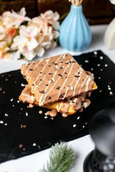 Vue latérale de la gaufre belge avec du chocolat au lait sur le dessus de la table