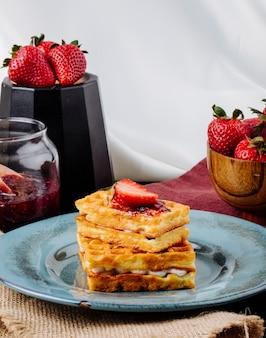 Vue latérale des gaufres à la crème à la vanille et à la confiture de fraises sur la table