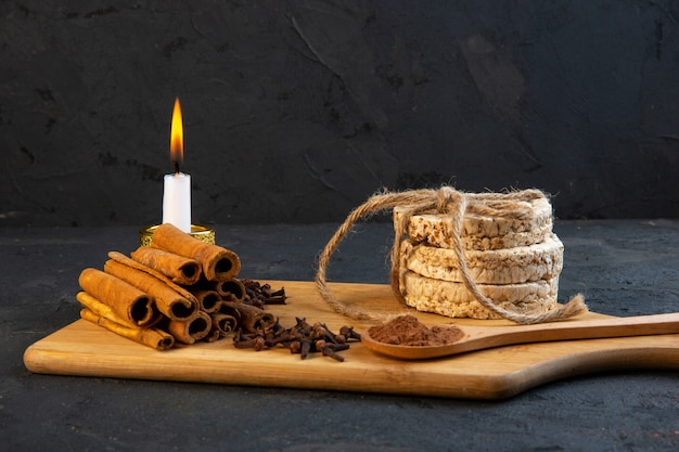 Vue latérale des gousses d'épices avec des bâtons de cannelle, des pains de riz attachés avec une corde et une bougie allumée sur une planche de bois