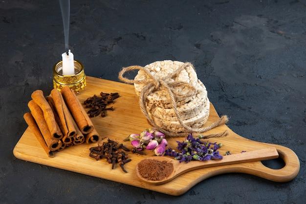 Vue latérale des gousses d'épices avec des bâtons de cannelle, des pains de riz attachés avec une corde rose thé et bougie sur planche de bois