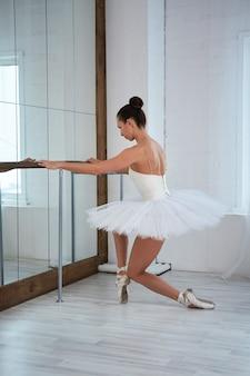 Vue latérale de la gracieuse ballerine pratiquant devant le miroir en studio. copysspace