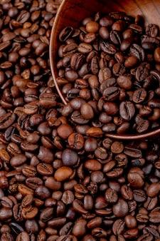 Vue latérale des grains de café torréfiés dispersés dans un bol en bois sur les grains de café