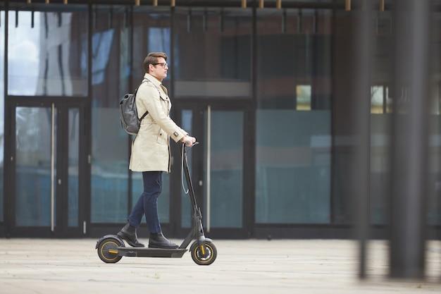 Vue latérale grand angle au jeune homme d'affaires moderne équitation scooter électrique tout en se rendant au travail avec les bâtiments de la ville urbaine en arrière-plan, copiez l'espace