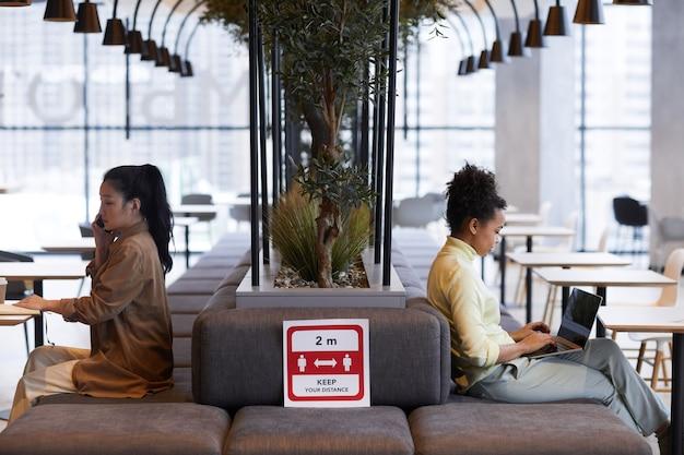 Vue latérale graphique sur deux jeunes femmes assises à des tables dans un café des côtés opposés avec signe de distanciation sociale au premier plan, espace pour copie