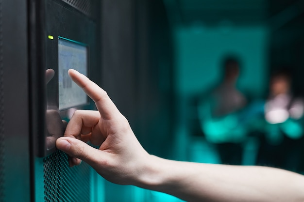 Vue latérale en gros plan d'une armoire de serveur d'exploitation d'un homme méconnaissable via un panneau de commande numérique dans un centre de données, espace de copie