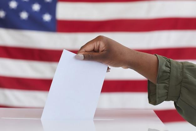 Vue latérale gros plan d'une femme afro-américaine méconnaissable mettant le vote dans l'urne contre la surface du drapeau américain, copy space