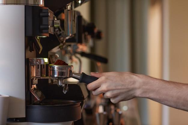 Vue latérale en gros plan d'une machine à café fonctionnant à la main tout en préparant du café frais au café, espace de copie