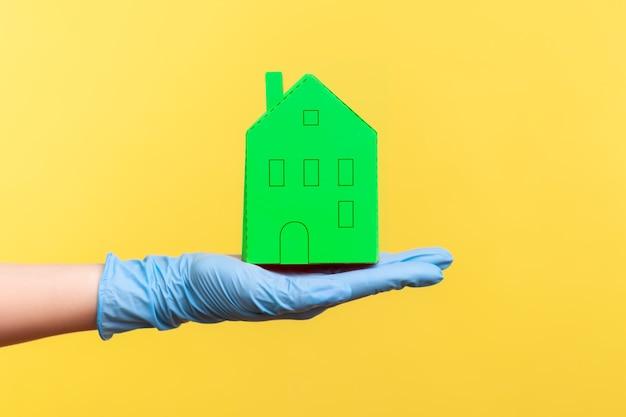 Vue latérale en gros plan de la main humaine dans des gants chirurgicaux bleus tenant l'extérieur de la maison en papier vert à la main.