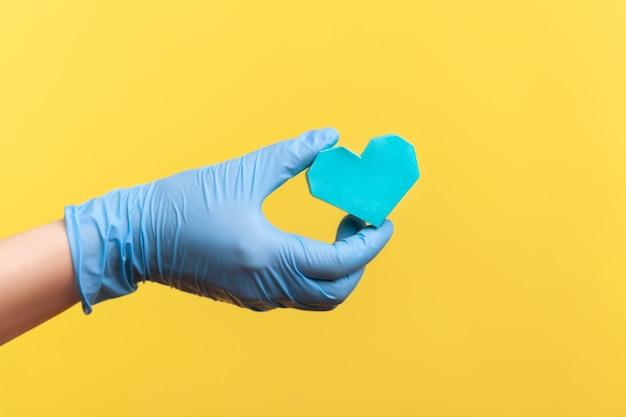 Vue latérale en gros plan de la main humaine dans des gants chirurgicaux bleus tenant une petite forme de coeur bleu à la main.