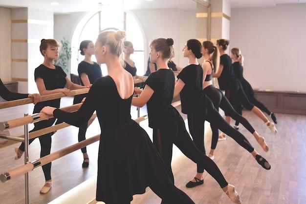 Vue latérale groupes de femmes effectuant des exercices au bar de la salle de sport en mettant l'accent sur l'athlétisme dans un concept de santé et de remise en forme.