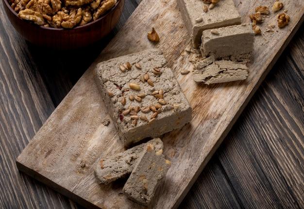 Vue latérale de halva avec des graines de tournesol sur une planche de bois et un bol de noix sur rustique