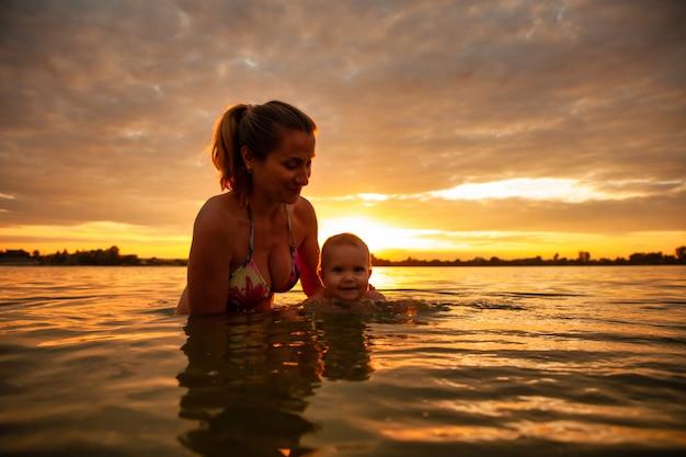 Vue latérale de l'heureuse mère caucasienne enseignant la natation petit beau bébé souriant dans l'eau de mer