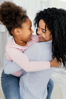Vue latérale de l'heureuse mère tenant sa fille smiley