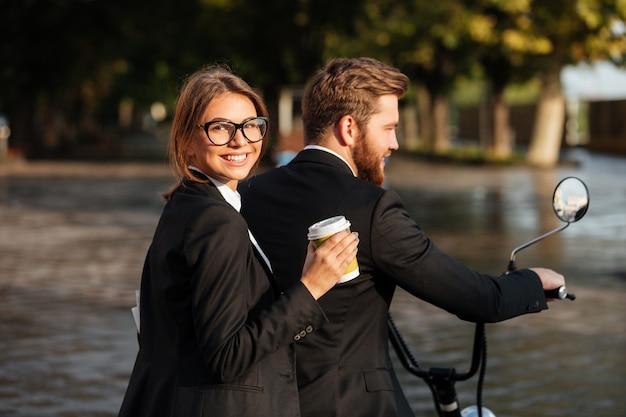 Vue latérale de l'heureux couple élégant monte sur une moto moderne
