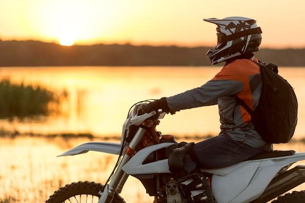 Vue latérale homme actif profitant d'une balade en moto