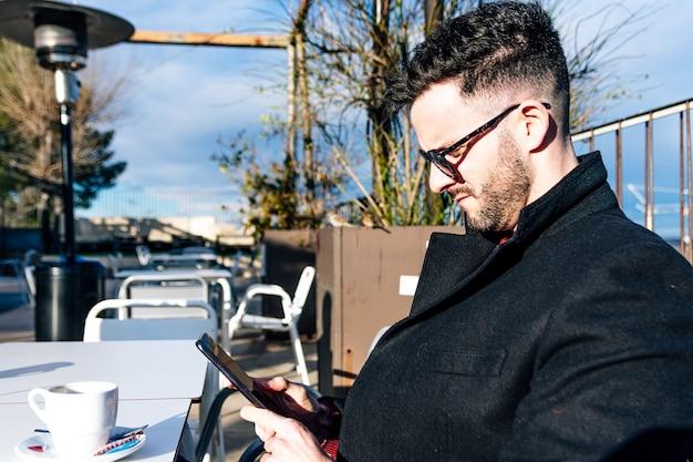 Vue latérale d'un homme d'affaires avec barbe taillée et lunettes de soleil prenant un café sur une terrasse de bar. utiliser son téléphone portable