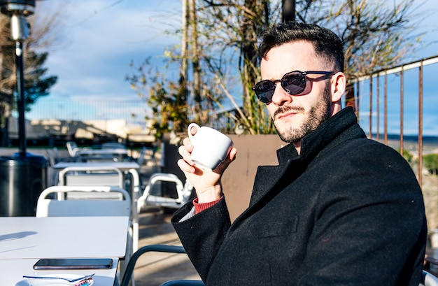 Vue latérale d'un homme d'affaires avec barbe taillée et lunettes de soleil prenant un café sur une terrasse de bar.