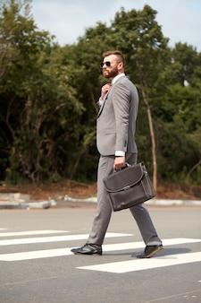 Vue latérale sur homme d'affaires caucasien en costume ou smoking marchant avec sac en mains