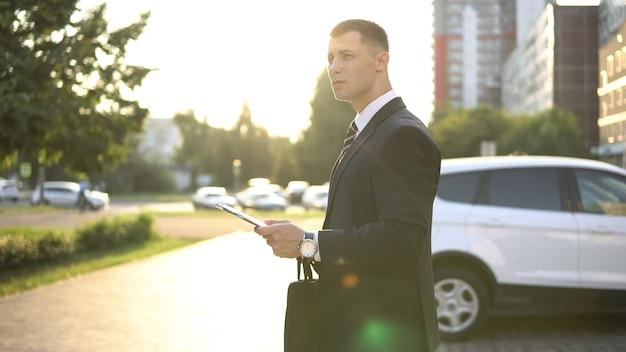 Vue latérale d'un homme d'affaires avec des documents en attente de réunion à l'extérieur près du centre d'affaires par beau temps.