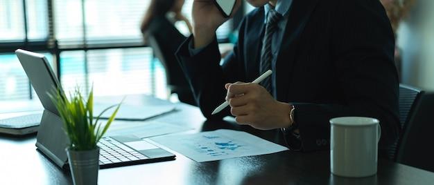 Vue latérale de l'homme d'affaires travaillant avec la paperasse et la tablette dans la salle de bureau