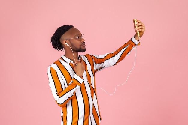 Vue latérale d'un homme africain faisant un selfie sur une caméra frontale de smartphone à l'aide d'écouteurs filaires.