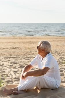 Vue latérale d'un homme âgé profitant de son temps à la plage