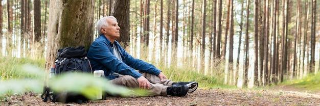 Vue latérale d'un homme âgé se reposant pendant la randonnée et profiter de la nature