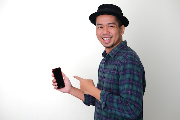 Vue latérale d'un homme asiatique cool souriant heureux tout en pointant vers son téléphone portable