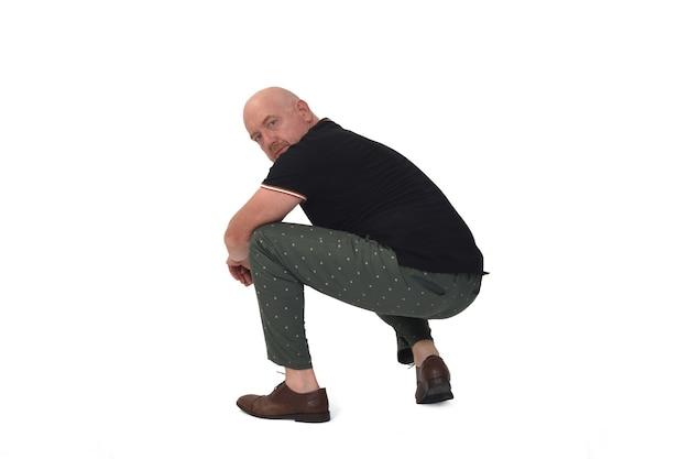 Vue latérale d'un homme assis accroupi sur fond blanc