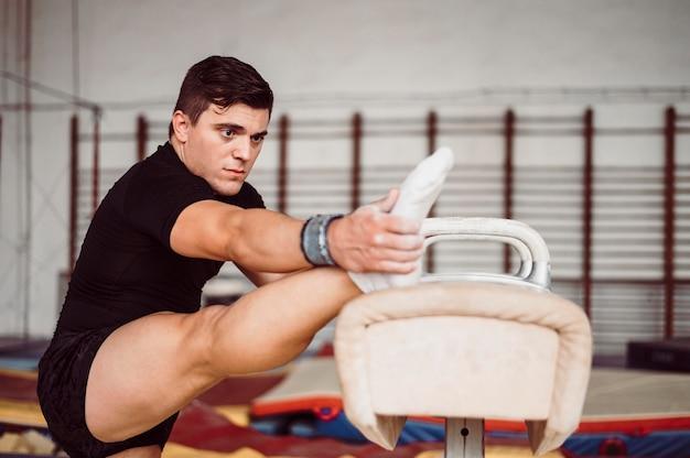 Vue latérale homme athlétique exerçant sur cheval d'arçons
