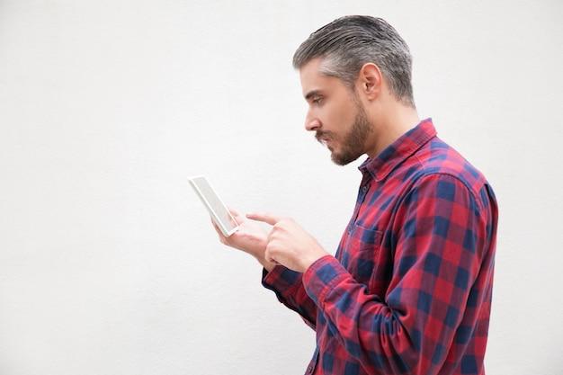 Vue latérale d'un homme barbu sérieux à l'aide de tablet pc