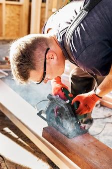 Vue latérale homme charpentier couper une planche de bois