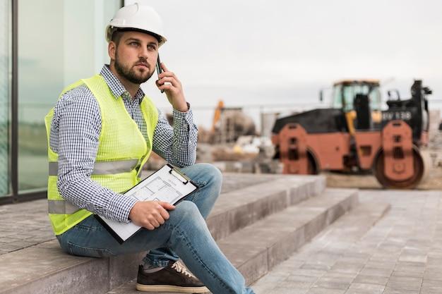 Vue latérale homme constructeur assis sur les escaliers