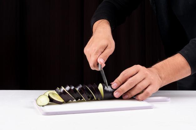 Vue latérale l'homme coupe l'aubergine en tranches dans une planche à découper avec un couteau sur le tableau blanc
