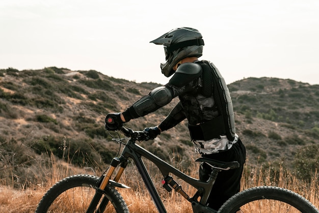 Vue latérale de l'homme dans l'équipement de vélo de montagne