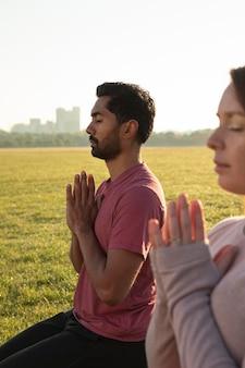 Vue latérale de l'homme et de la femme méditant à l'extérieur