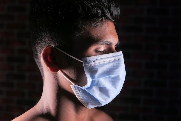 Vue latérale de l'homme a fermé les yeux avec un masque protecteur isolé sur fond noir