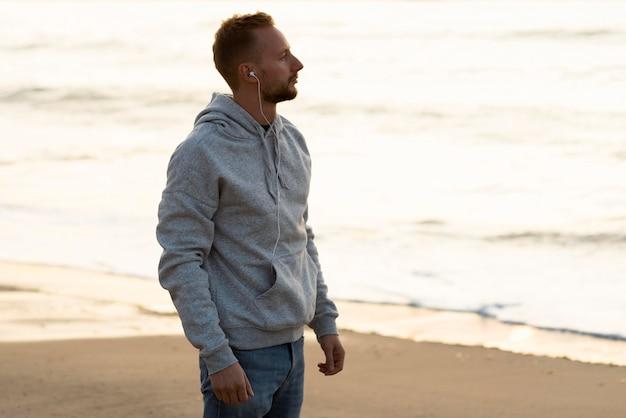 Vue latérale homme jogging sur le sable tout en écoutant de la musique