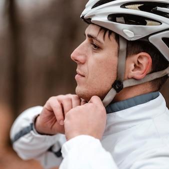 Vue latérale de l'homme mettant un casque de sécurité pour le vélo