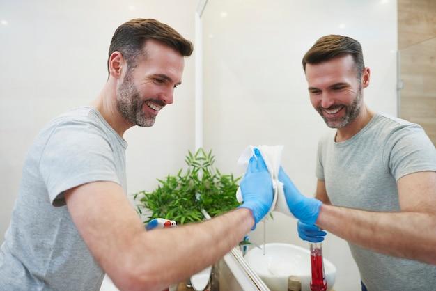 Vue latérale d'un homme nettoyant un grand miroir dans la salle de bain